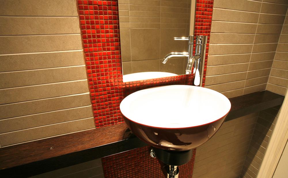 חדר שירותי אורחים הכולל כיור עילי ומראה על רקע פסיפס אדום