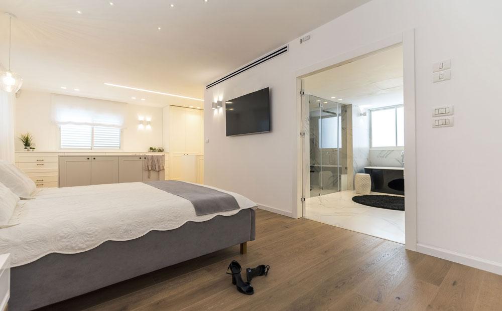 חדר שינה מעוצב עם פרקט עץ גושני וחדר רחצה גדול